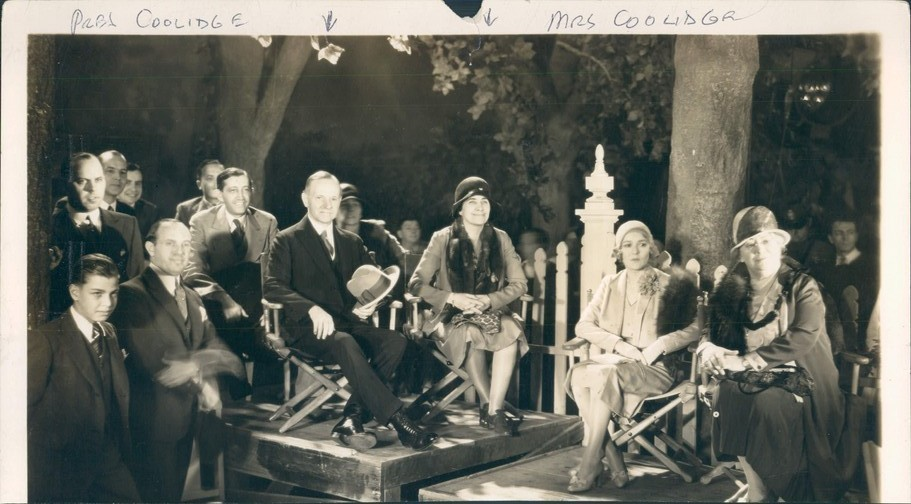 Ex-President Calvin Coolidge watches with keen interest the progress of making the Vitaphone operetta, Viennese Nights at Warner Brothers movie set.  On the set with them are J.L. Warner, Will H. Hayes, and Mrs. C Young, wife of the Governor of California.  7/24/1930.